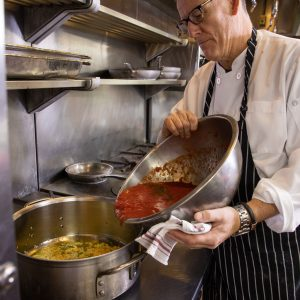 Chef tips a bowl of tomato sauce into a pan
